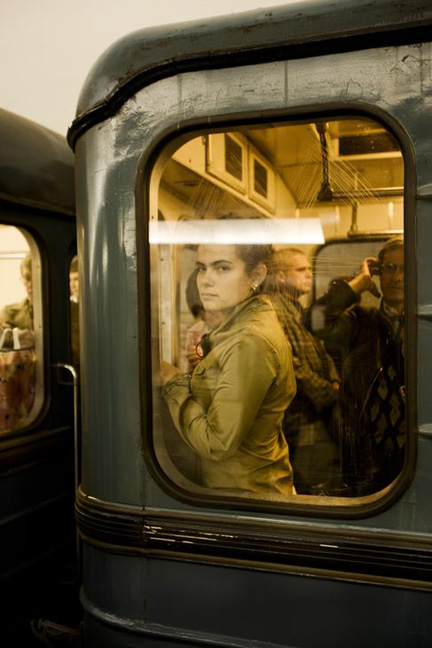 Woman Looking Through The Window Of A Subway Car, Moscow, Russia.
